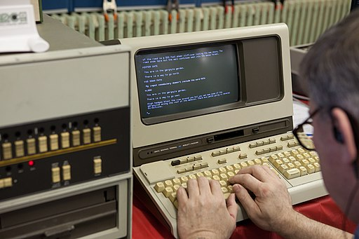 A picture of a man with glasses using an old terminal display from 1978